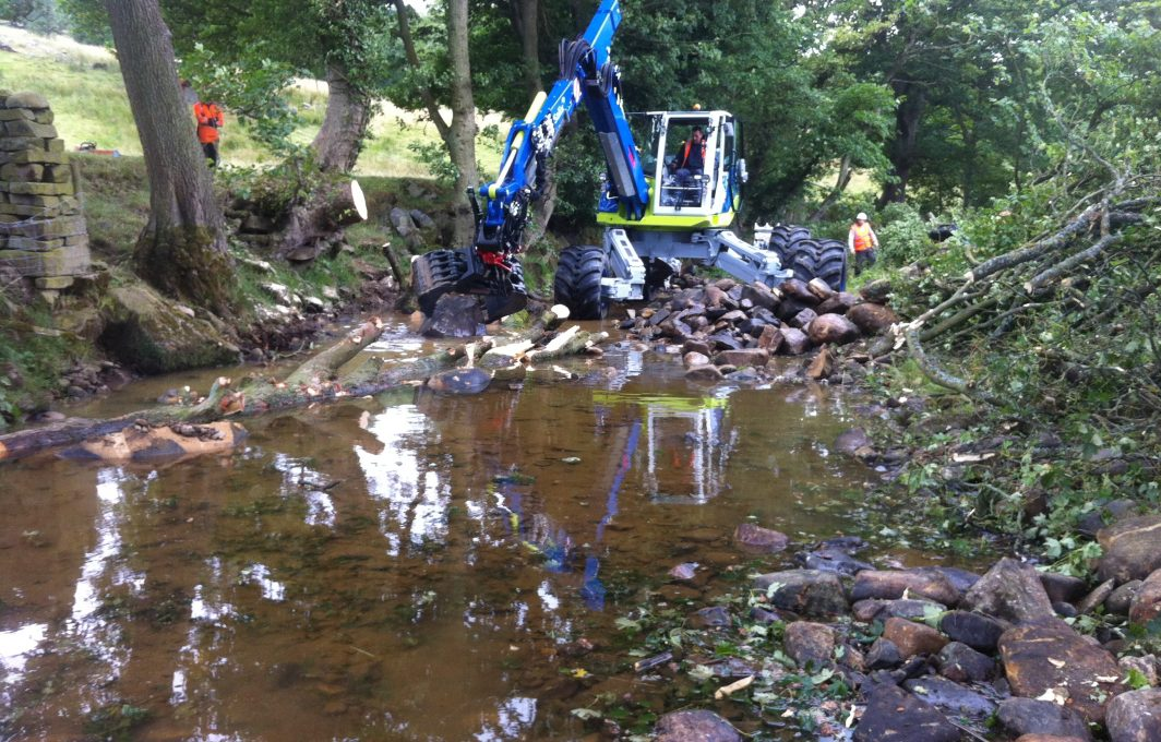 Spider excavator moving boulders within the river